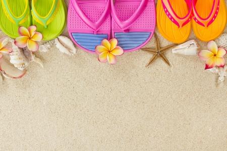 シェルとプルメリアの花夏ビーチ コンセプトに砂の中のカラフルなフリップフ ロップ