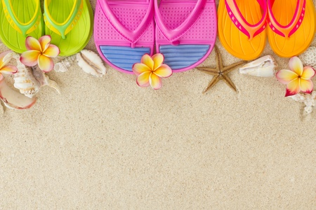 Colourful Flip Flops in the sand with shells and frangipani flowers  Summertime on beach concept