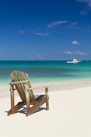 Beach chair on white sand beach with white boat on background  Summer Holiday background