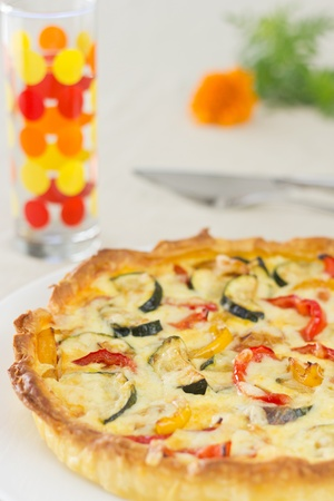Home made vegetable quiche with colorful glass and orange flower on background Stock Photo