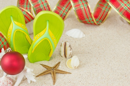 Flip Flops in the sand with shells and Christmas decoration  Xmas summertime on beach concept