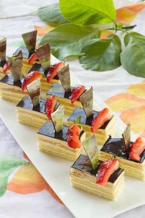 Group of Mini square sponge cakes with strawberry and triangular chocolate decoration