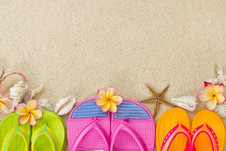 flip flops: Flip Flops in the sand with shells and frangipani flowers  Summertime on beach concept