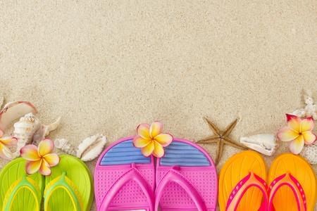 sandalias: Fracasos de tirón en la arena con conchas y Summertime frangipani flores en concepto de playa Foto de archivo
