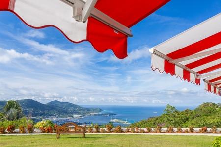 ベンチと海を望む日当たりの良い明るい青空に日除け