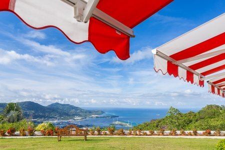 an awning: Awning over bright sunny blue sky with bench and sea view  Stock Photo