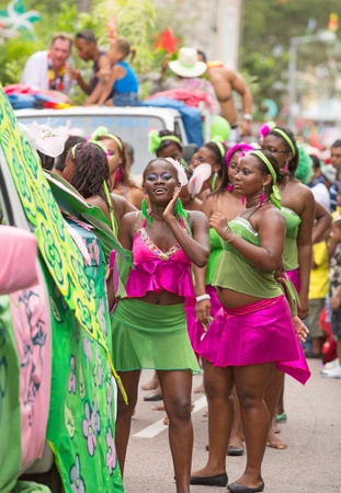 Victoria, Seychelles - February 9, 2013: Group of young women in vibrant green and pink outfit dancing on streets of Victoria, on Parade of Seychelles international Carnival Stock Photo - 18777501