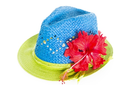Blue and green summer panama straw hat with red hibiscus flower isolated on white photo