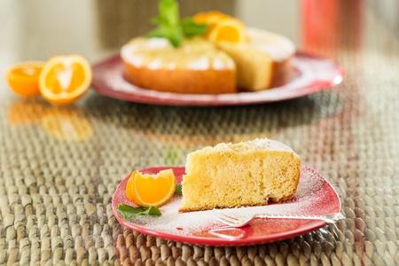 orange cake: Slice of freshly cooked orange cake, with whole cake on background