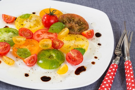 lunares rojos: Colorida ensalada de tomate con rojo de lunares tenedor y cuchillo Foto de archivo