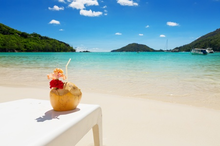 Tropical Cocktail in coconut shell with red hibiscus flower, on white beach chair, with perfect blue lagoon background Stock Photo - 21742217