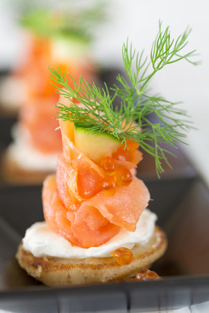 blini: Blini with smoked salmon and sour cream, garnished with dill  Close-up view