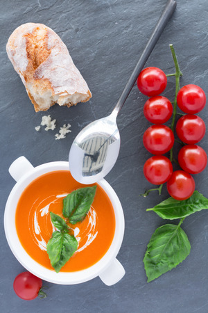 Overhead view of a bowl of tomato soup drizzled with cream and garnish with leaves of fresh green basil photo