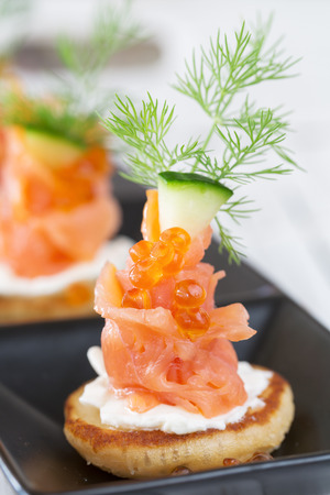 Smoked salmon and sour cream appetiser, garnished with dill  Close-up view