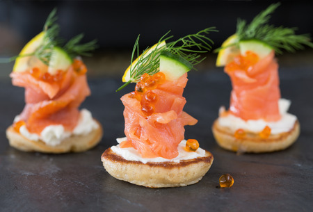 Blini with smoked salmon and sour cream, garnished with dill  Close-up view on dark background