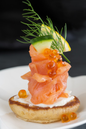 Appetizer with smoked salmon and sour cream, garnished with dill  Close-up view photo