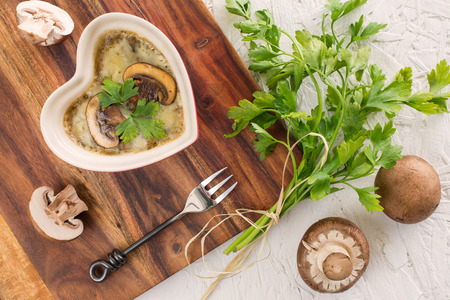 mushroom casserole in heart shape  with fresh parsley and cheese on brown wooden board photo