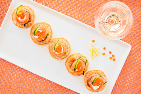 blini: Smoked salmon and caviar appetizer with cream fresh and cucumbers on blini, top view
