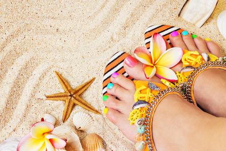pedicura: Pies femeninos con pedicure bastante multicolor sobre la arena, con flores frangipani y conchas marinas. Concepto Summertime
