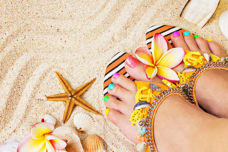 Female feet with pretty multicolor pedicure on sand, with frangipani flowers and seashells. Summertime concept Standard-Bild