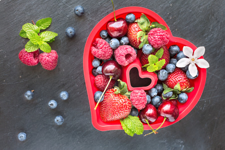 石の灰色の背景は上面にハートの形の赤いシリコン バッキング型の新鮮な果実のミックス 写真素材