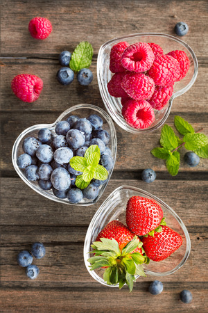 natural health: Mix of fresh berries in a glass ramekins in shape of heart on wooden background top view