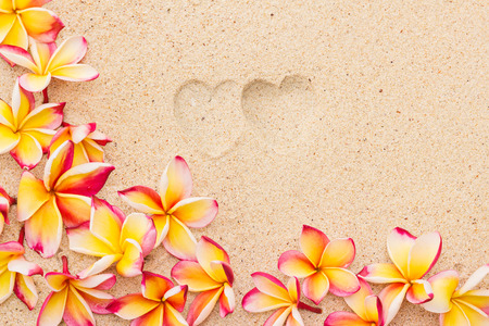 Two heart print on sand with frangipani flowers top view horizontal composition
