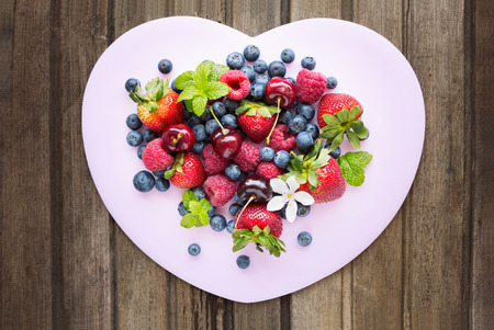 Mix of fresh berries in three  glass ramekins in shape of heart, on wooden background, top view, horizontal composition Stock Photo