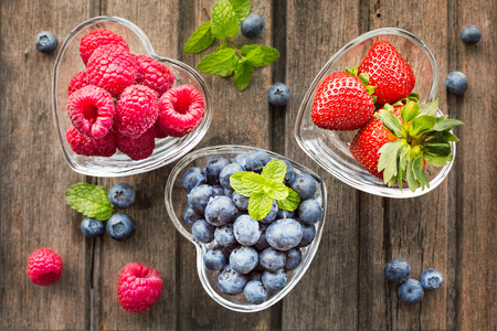 summer diet: Mix of fresh berries in three  glass ramekins in shape of heart, on wooden background, top view, horizontal composition Stock Photo