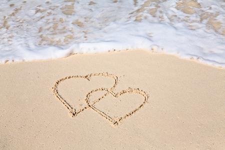 ビーチの砂に描かれた二つの心 写真素材