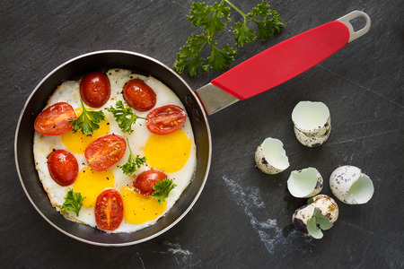 eggs: Sunny side up quail eggs fry with tomato and parsley, top view, horisontal composition Stock Photo