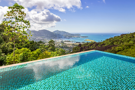 Stunning panoramic view of Mahe island, Seychelles from crystal clean blue swimming pool