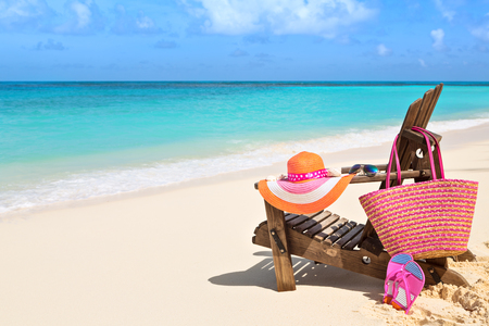 chairs: Chair with bag, hat, flip-flops and sunglasses on sunny beach, tropical beach vacation and travel concept Stock Photo