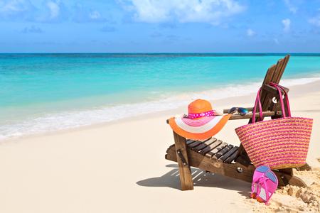 vacaciones en la playa: Silla con el bolso, sombrero, chanclas y gafas de sol en la playa soleada, vacaciones en la playa tropical y el concepto de viaje