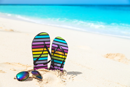 flipflops: Multicolored flip-flops and sunglasses on a sunny beach.Tropical beach vacation and travel concept