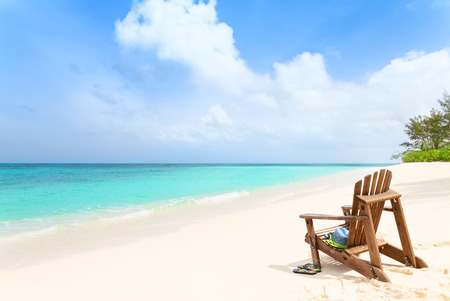 Wooden beach chair with hat, sunglasses and slippers at tropical beach, summer holiday concept Foto de archivo