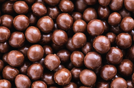 colorant: Brown chocolate dragee balls background, top view, close up Stock Photo