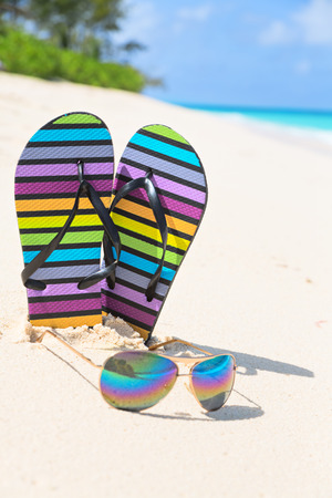 vertical composition: Multicolored flip-flops and sunglasses on a sunny beach.Tropical beach vacation and travel concept, vertical composition