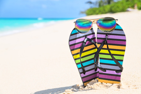 flipflops: Multicolored flip-flops and sunglasses on a sunny beach. Tropical beach vacation and travel concept, vertical composition
