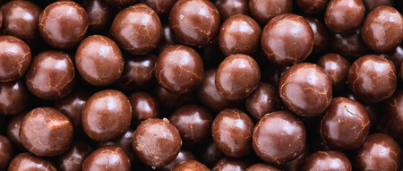 colorant: Brown chocolate  dragee balls background, close up, top view, letterbox format