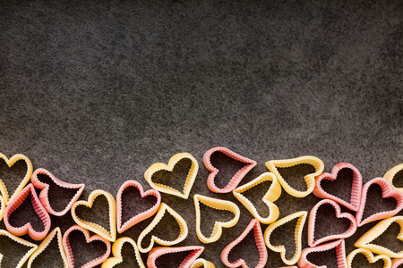 yellow heart: Red and yellow heart shaped pasta, top view, copy space, food background Stock Photo