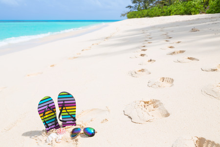 flipflops: Multicolored flip-flops and sunglasses on a sunny beach. Tropical beach vacation and travel concept Stock Photo
