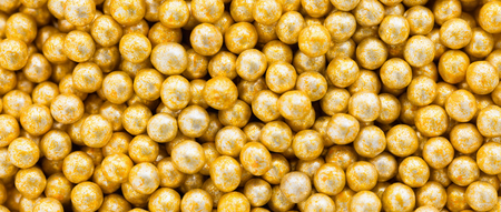 colorant: Golden dragee balls background, letterbox, top view Stock Photo