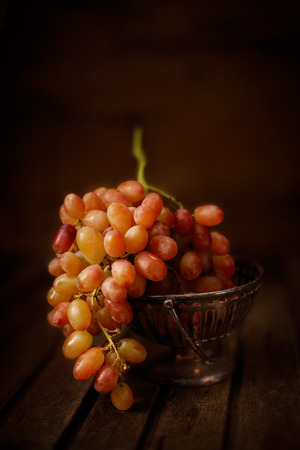 vertical composition: Fresh grapes in small metal vase on wooded background, vertical composition
