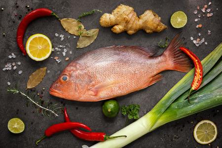 Los ingredientes frescos para cocinar pescado, pargo rojo, fuga, lima, limón, perejil, ají, jengibre. Vista superior Foto de archivo - 62001271