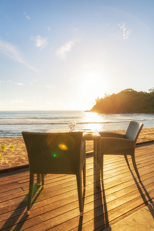two chairs: Dining table and two chairs on decking by sea side at evening sun light. Vertical composition
