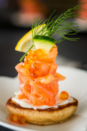blini: One Blini appetizer with smoked salmon and sour cream, garnished with dill. Close-up view Stock Photo