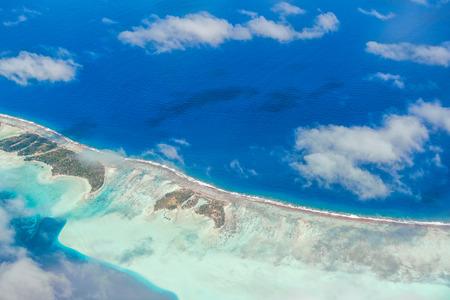 Vue aérienne de l'île avec des nuages, récif et le lagon. Île près de Tahiti dans l'archipel tropical de la Polynésie française dans l'océan Pacifique. Banque d'images