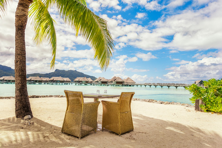 otemanu: Two chairs and table on a sand beach with a view on the lagoon and Mount Otemanu on the tropical island of Bora Bora, near Tahiti, in French Polynesia.