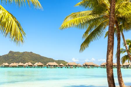 borabora: View of the Otemanu mountain and bungalow with palm tree and stunning lagoon. Bora-Bora. Tahiti. Polynesia Stock Photo